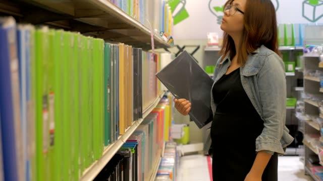 vidéos et rushes de femme enceinte en choisissant le document dossier de papeterie - fournitures scolaires