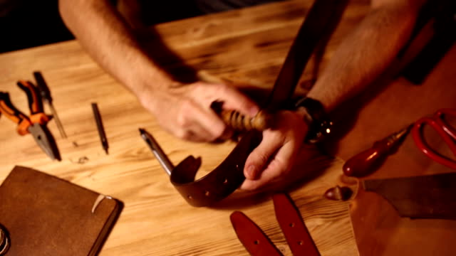 Working process of the leather belt in the leather workshop. Man holding crafting tool and working. Tanner in old tannery. Wooden table background video