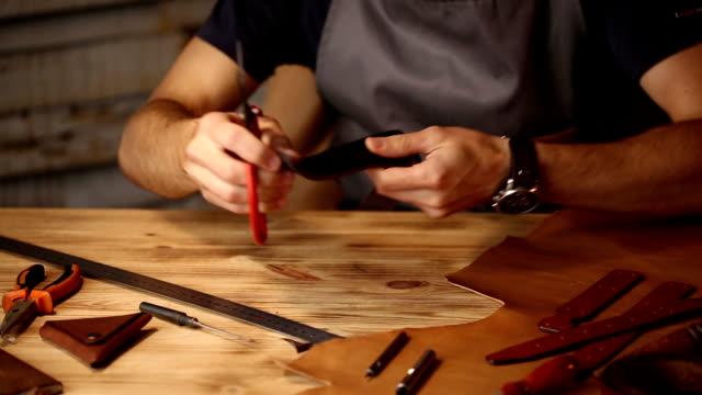 Processus de travail de la ceinture de cuir dans l'atelier de cuir. Un artisanat outil holding de l'homme et travail. Tanner dans l'ancienne tannerie. Fond de table en bois - Vidéo