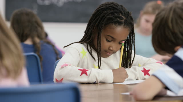 Working Quietly A young girl writes with pencil on paper in classroom. The other students are also working independently. elementary age stock videos & royalty-free footage