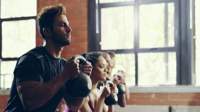 vídeos de stock e filmes b-roll de working through the squat - agachar se