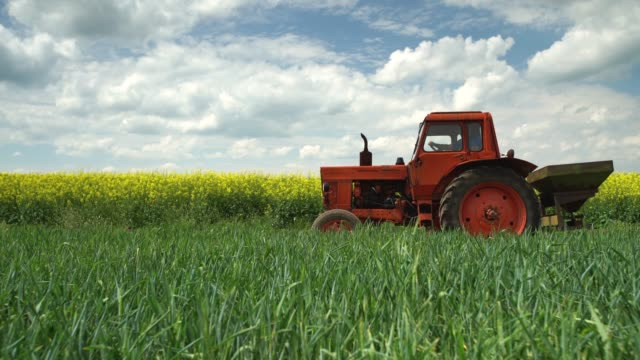 Working tractor in the agricultural fields and dramatic clouds video