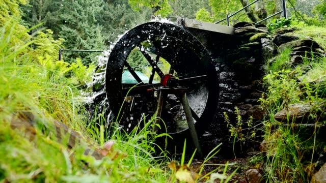 Working water wheel driving generator on mountain stream video