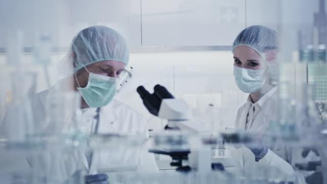 arbetar med biohazardous substans. kvinna och man under forskning - corona vaccine bildbanksvideor och videomaterial från bakom kulisserna