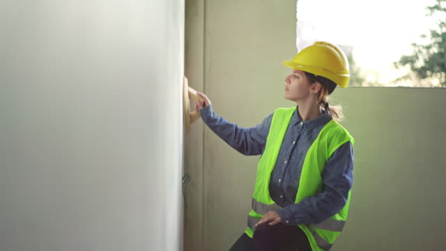 Working woman plastering walls inside at construction site