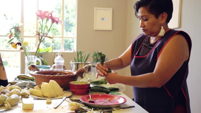 vídeos de stock, filmes e b-roll de mãe da classe trabalhadora cozinhando tamales com negro mole em casa - tradição