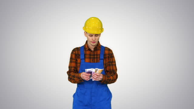 A workman counting cash in exaggerated way and dancing after that on gradient background