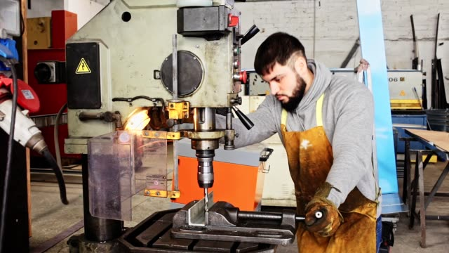 stockvideo's en b-roll-footage met werkman die metaaldelen op stationaire machine in metaalbewerkingsworkshop boort - metaalbewerking