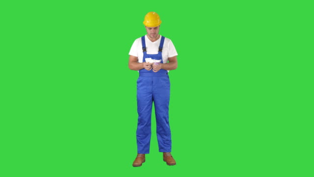 A workman excitedly counting his salary on a Green Screen, Chroma Key