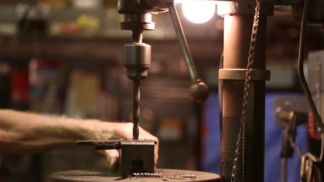 Workman in shop using a drill press video