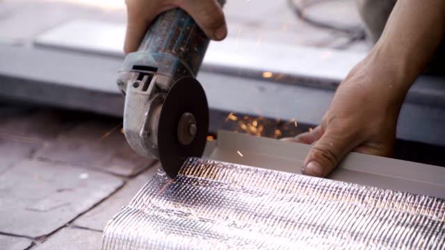arbeiter verwenden schleifmaschine handheld, um das dach zu schneiden und zu machen. - kreissäge stock-videos und b-roll-filmmaterial