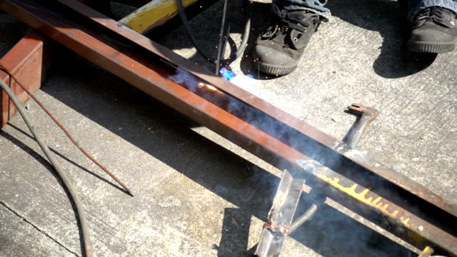 workman welding steel on the part of home construction at the outdoor site location video