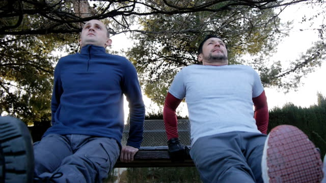 Workout with personal trainer outdoors. Low angle view of two fitness men doing triceps bench dips in a park as part of a workout routine. Workout with personal trainer outdoors. Low angle view of two fitness men doing triceps bench dips in a park as part of a workout routine dipping sauce stock videos & royalty-free footage