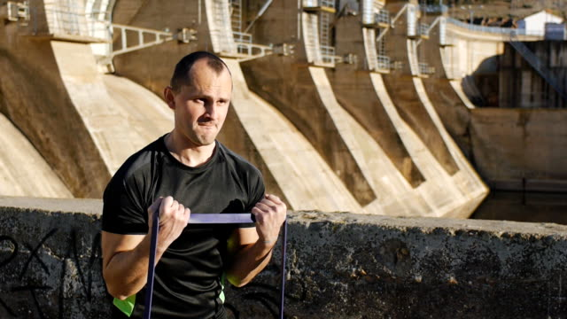 Workout with personal trainer outdoors. Male athlete in black t-shirt doing concentration curl with resistance band on river dam background. video
