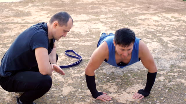 Workout with personal trainer outdoors. Strong man doing push-ups on concrete floor being controlled by male coach. video