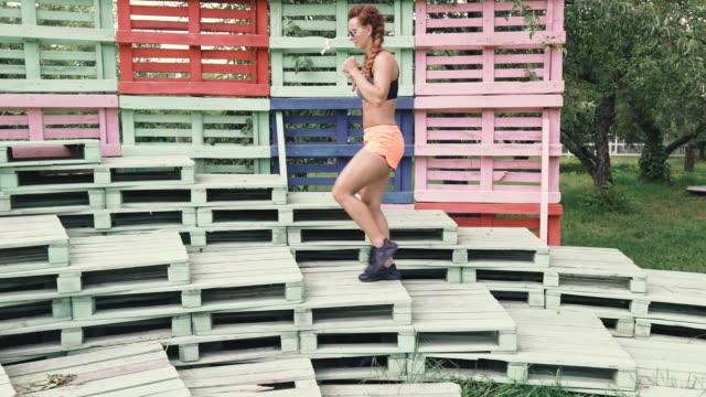 workout. young woman shows sport exercise on the street. - staw człowieka filmów i materiałów b-roll