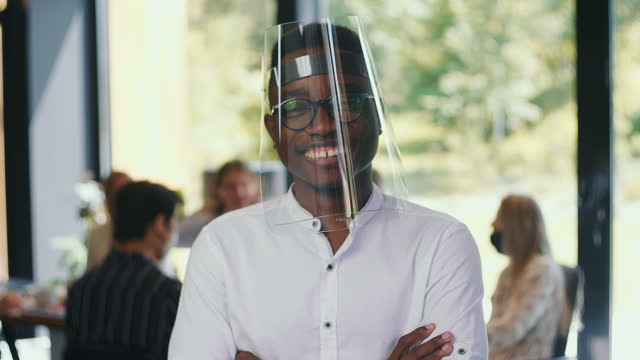 Workplace safety. Portrait of young 20s African businessman in plastic face shield smiling at light office slow motion.