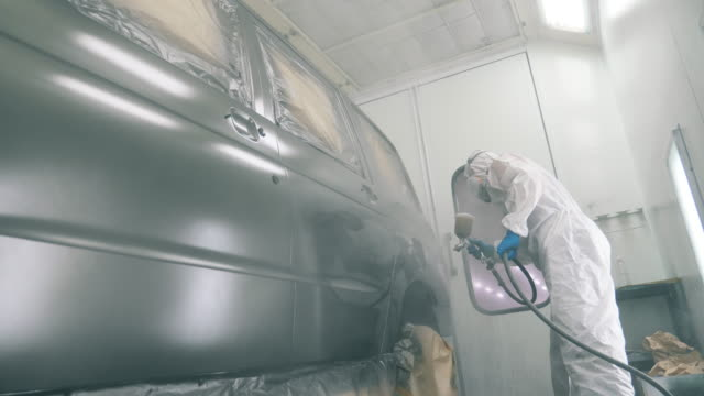 Workshop with an automobile getting dyed by the repairman video