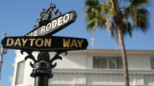 stockvideo's en b-roll-footage met wereldberoemd rodeo drive symbool, cross street sign, intersection in beverly hills. toeristisch los angeles, californië, vs. rijke rijke leven consumentisme, luxe merken en high-class winkels concept. - glamour