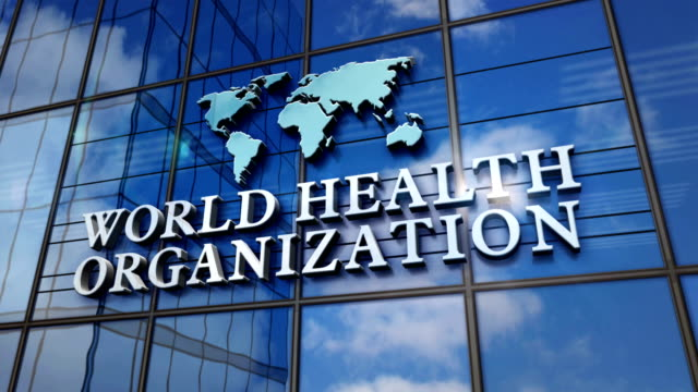 world health organization building with glass wall and mirrored building - quartiere generale video stock e b–roll