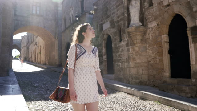 World Traveler Young caucasian woman walking down the Street of the knights templar in Rhodes town - Rhodes island, Greece. knight person stock videos & royalty-free footage