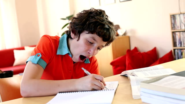 Worn out from doing homework A pre-teen boy finishes up some writing in his notebook before yawning,  yawning stock videos & royalty-free footage