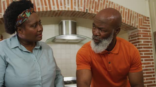 vídeos de stock, filmes e b-roll de casal de idosos afro-americano preocupado com contas usando laptop na cozinha em casa - bico