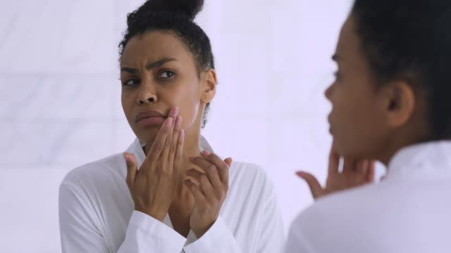 worried african lady upset with dry skin looking in mirror - spa facial stock videos & royalty-free footage