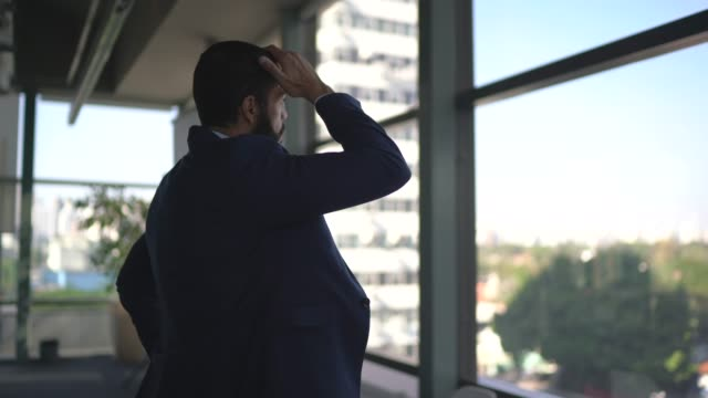 Worried businessman looking through window contemplating on the office