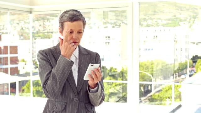 Worried businesswoman using her smartphone