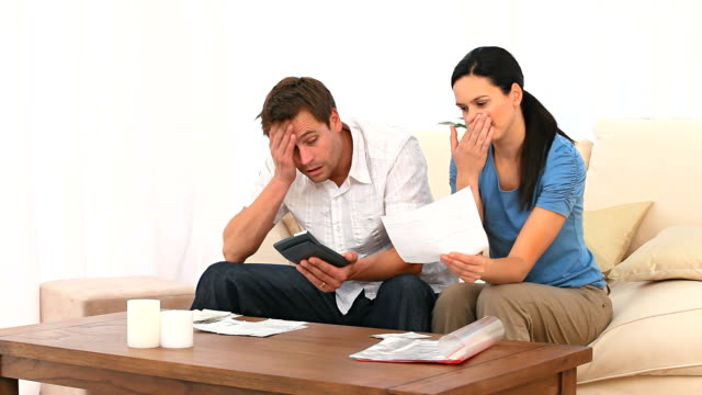Worried couple calculating their domestic bills video