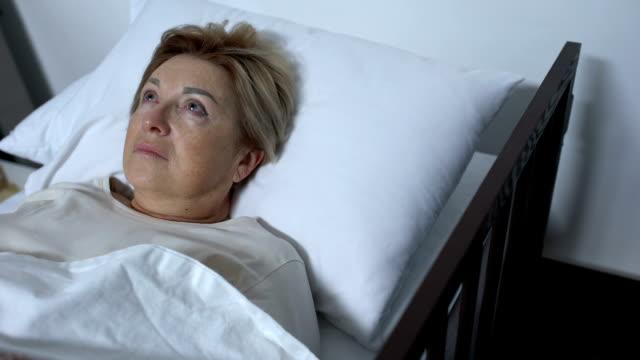 vídeos y material grabado en eventos de stock de paciente anciano preocupado acostado en la cama y mirando alrededor, la enfermedad de alzheimer - geriatría