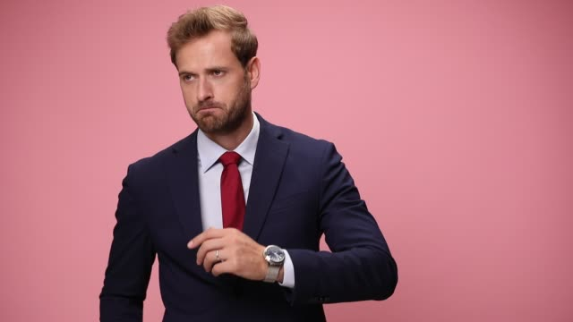 worried elegant young businessman checking time, being late, holding hands behind neck and thinking, looking to side, frowning and moving on pink background