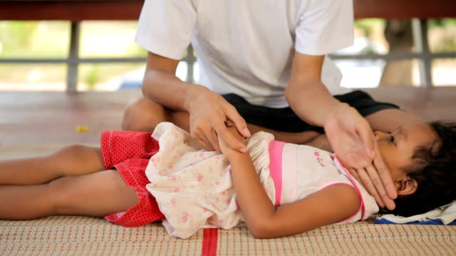 Worried father holding sick child in home video