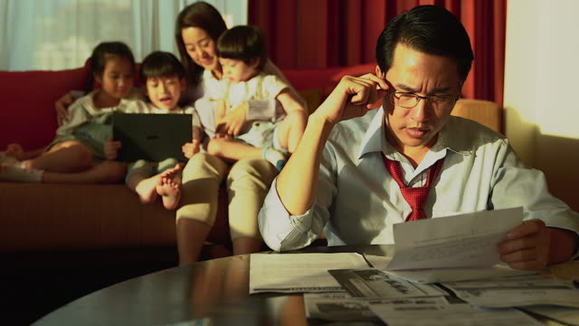 A worried father looking at the financial bill in his hand, in the background of his family playing tablet.