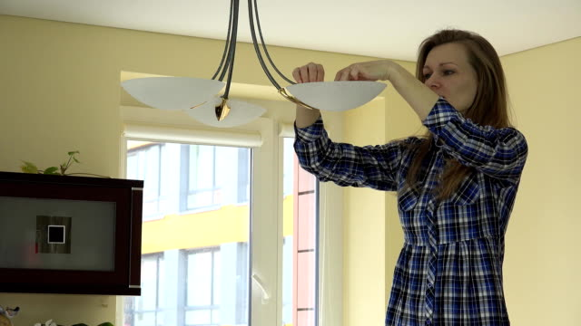 Worried girl woman unscrew eco light bulbs from chandelier. video