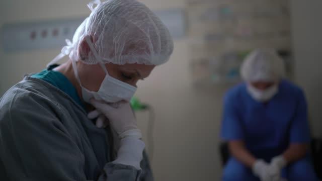 stockvideo's en b-roll-footage met ongerust gemaakte gezondheidszorgmedewerkers bij werkende ruimte in het ziekenhuis - moe