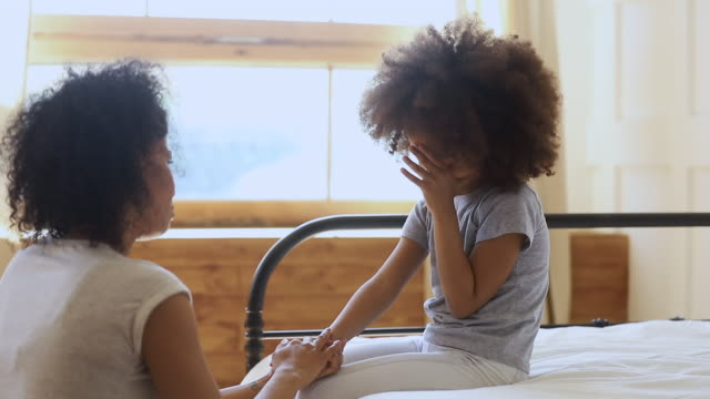 worried loving african mother holding hand comforting upset kid daughter - chiedere scusa video stock e b–roll