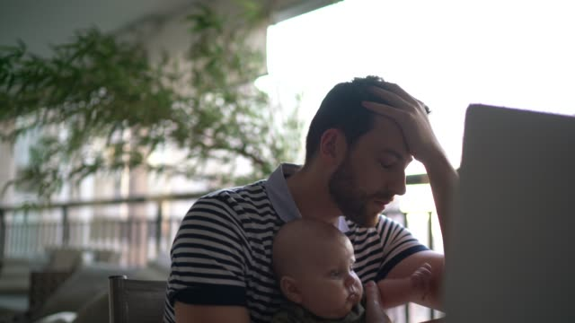 Worried man holding son and working with laptop at home