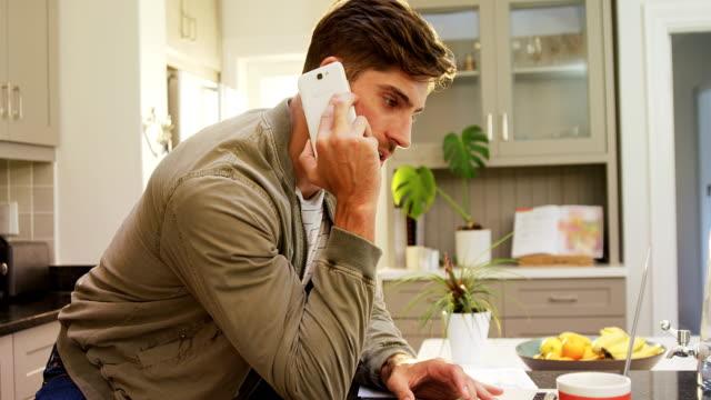 vidéos et rushes de l'homme inquiet parler au téléphone tout en utilisant son ordinateur portable 4k 4k - cuisine non professionnelle