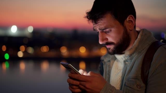 besorgter mann mit handy bei sonnenuntergang - online dating stock-videos und b-roll-filmmaterial