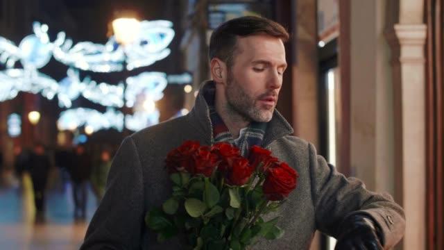 vídeos de stock e filmes b-roll de worried man with bunch of roses waiting for his lady - passagem de ano