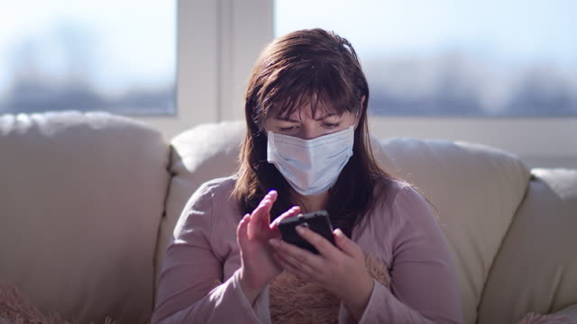 worried masked woman on the couch talking on the phone, explains something video