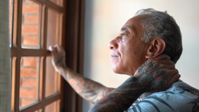 Worried mature man looking through window contemplating and thinking at home Worried mature man looking through window contemplating and thinking at home human age stock videos & royalty-free footage