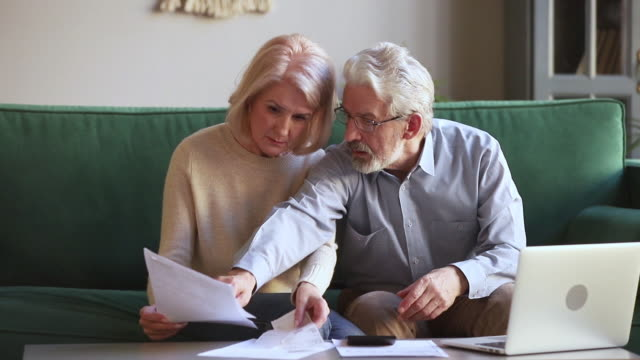 Worried old couple stressed about unpaid bank debt holding bills Worried senior old couple stressed about paperwork discuss unpaid bank debt holding bills check expenses, retired aged family read loan payments documents talking at home anxious about money problems bills and taxes stock videos & royalty-free footage