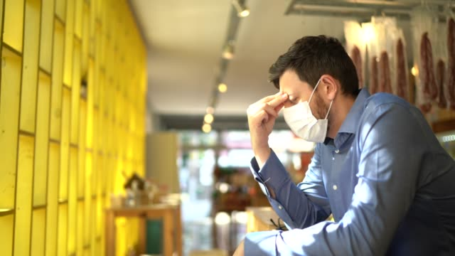 worried owner with face mask at his small business - stress emotivo video stock e b–roll