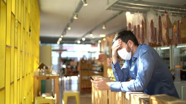 worried owner with face mask using mobile phone at his small business - businessman covid mask video stock e b–roll