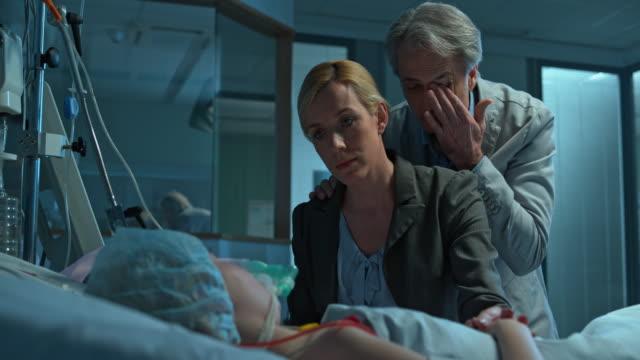 ds oroliga föräldrar besöker ett sovande barn efter sin operation - intensivvårdsavdelning bildbanksvideor och videomaterial från bakom kulisserna