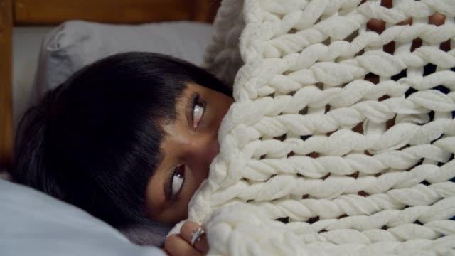 worried pretty woman hiding under duvet in bed - kołdra filmów i materiałów b-roll