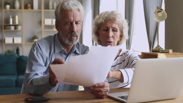 Worried senior couple checking calculating bills discuss unpaid debt taxes Worried senior retired couple checking calculating bills bank loan payment doing paperwork discuss unpaid debt taxes, stressed old grandparents family look at laptop upset about money problem concept financial bill stock videos & royalty-free footage